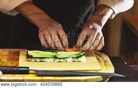 Cook Hands Making Japanese Sushi Roll. The Process Of Cooking Sushi Roll With Salmon, Cucumber, Rice