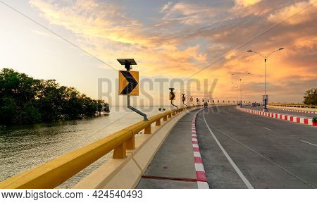 Curve Concrete Road With Curve Traffic Sign Beside The Sea At Sunset Time. Solar Panel Energy On Yel