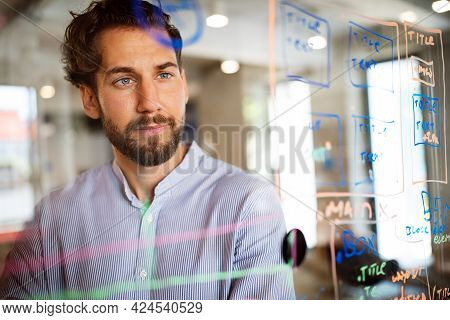 Handsome Man Working And Writing On Glass Board In Office. Business, Technology, Research Concept