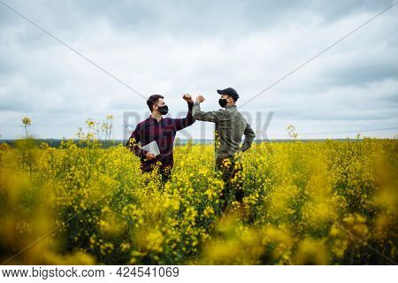 Two Farmers Greet Each Other During Coronavirus Pandemic In The Middle Of The Rapeseeds Field. Farme