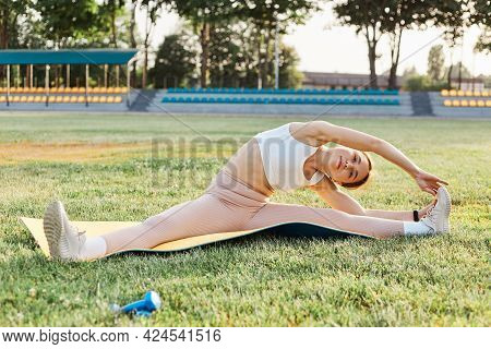 Outdoor Shot Of Dark Haired Female Wearing White Top And Beige Leggins, Sitting On Karemat, Doing Cr