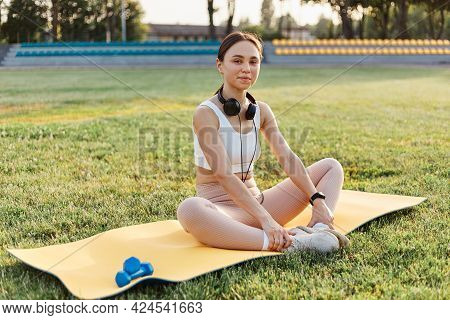 Beautiful Young Female Wearing White Top And Beige Leggins Sitting On Yellow Karemat With Headphones