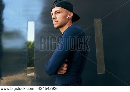 Bottom View Of An Athletic Man Taking A Break After Workout In The City Street. Athlete Male In Spor