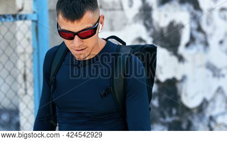 Sporty Man In Blue Sportswear, Backpack And Sunglasses Walking On The City Street. Sportsman Going T