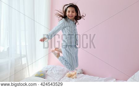 Full-length Of A Caucasian Cheerful Little Girl In Blue Pajama Dancing In Modern Cozy Sunny Bedroom