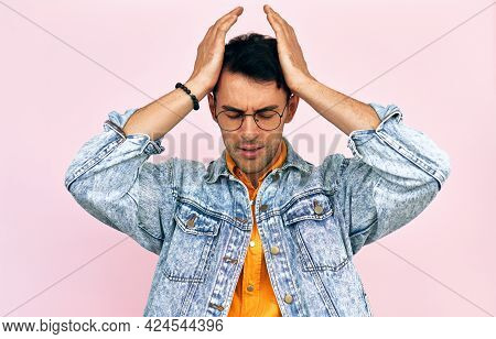 Studio Image Of A Frustrated Young Man Dressed In A Denim Jacket And Transparent Spectacles Keeping