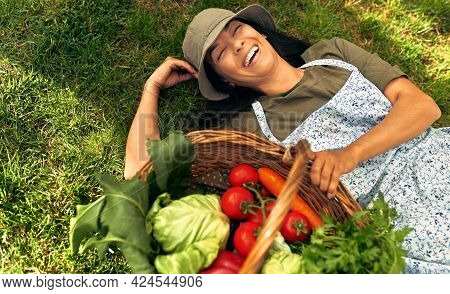 View From Above Of A Gorgeous Female Gardener Lying On The Grass With A Basket With Freshly Picked E