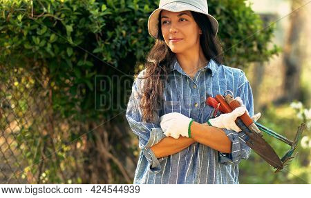 Portrait Of A Pretty Female Gardener Posing With Garden Tools In The Garden. A Young Woman Gardening