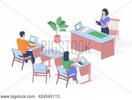 Teacher Lectures In Modern Classroom. Students Sitting Desks With Laptops And Books. Woman With Tabl