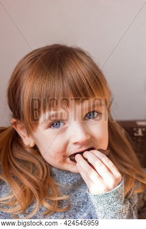 Little Girl Bites Chocolate Portrait Close-up, Children's Emotions Happy Childhood, Harm Of Sweets F