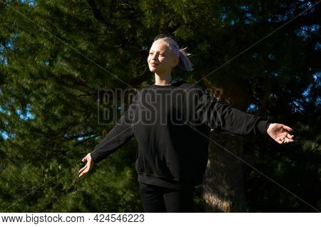 Teen Girl, Arms Outstretched, Rejoices In The Sun And Wind On The Background Of A Large Tree
