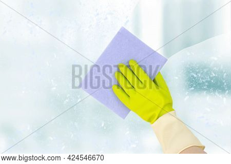 Spring Cleaning Concept. Top View Of Hand In Yellow Rubber Gloves Cleaning The Window With A Soft Ra