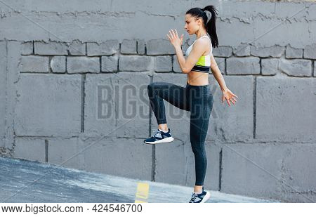 Horizontal Side View Of Athlete Young Woman Jumping Exercises On A Concrete Grey Wall. Caucasian Fem