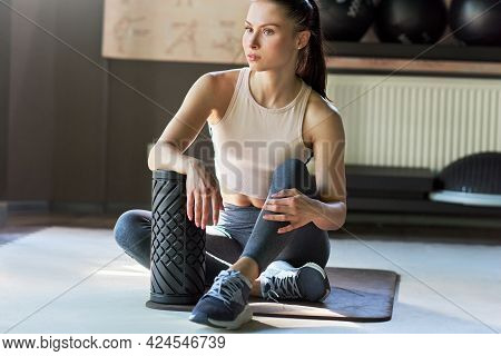 Horizontal Shot Of Young Woman Relaxing After Stretching Exercises At The Gym. Athletic Girl In The
