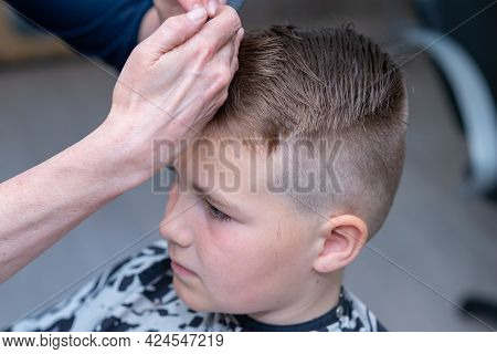Cute European Boy Getting Hairstyle, Hairdresser Makes A Hairstyle For A Boy.toned.side View.closeup