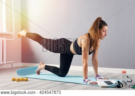 Woman In Fitness Wear Doing Exercise At Home. Time For Yoga. Healthy Girl Doing Exercises While Rest