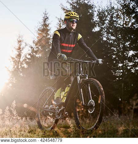 Young Man In Cycling Suit Riding Bicycle On Grassy Hill With Morning Sunlight And Trees On Backgroun
