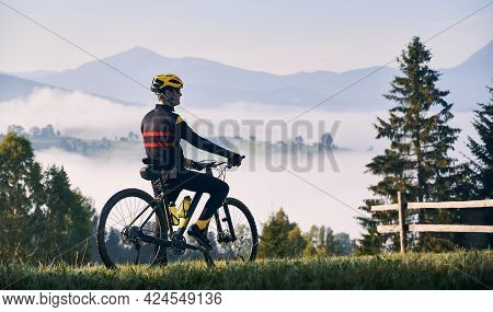 Cyclist Standing With Bicycle On Grassy Hill And Looking At Beautiful Misty Mountains. Male Bicyclis