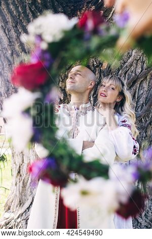 Young People Are Posing In Traditional Folk Costumes. Cossacks Man And Woman In Wreaths And Embroide