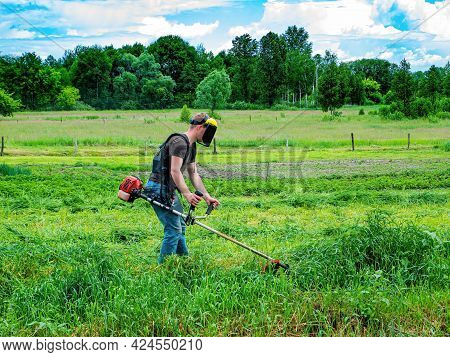 A Man Is Cutting Green Grass With A Lawnmower. A Grass Trimmer. Mow The Grass. Use A Lawn Mower To M