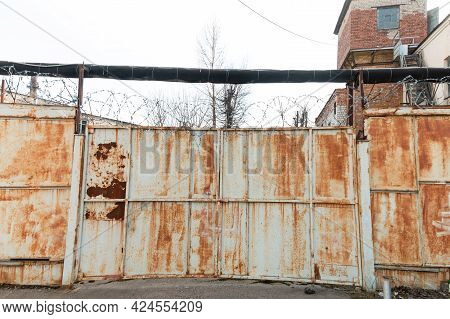 Barbed Wire On Rusty Iron Doors And Walls. Jail.
