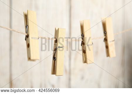 Clothespins On Rope Against White Wooden Background, Closeup