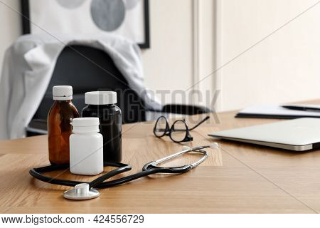 Bottles With Medicaments, Laptop And Stethoscope On Table Indoors, Space For Text. Modern Medical Of
