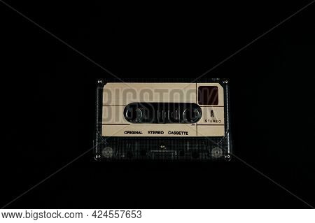 Audio Cassette On A Black Background. Compact Tape Cassette An Analog Magnetic Tape Recording Format