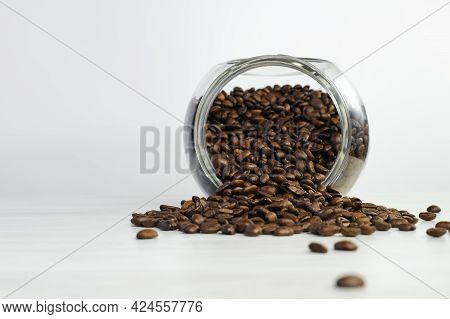 Spilled Roasted Coffee Beans From Glass Jar On White Table.  Coffee Beans In A Coffee Shop For Tasti