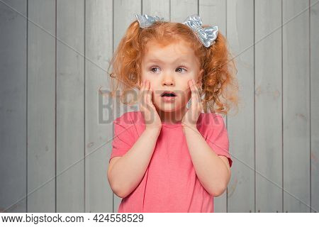 Shocked And Scared Redhead Little Girl 4-6 Years Old, Staring Startled At Left And Frightened, Afrai