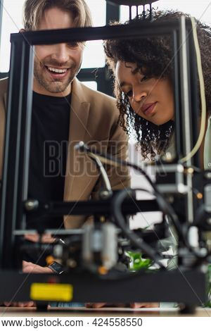 Positive Young Interracial Colleagues Looking At 3d Printer Producing Plastic Figure In Modern Offic