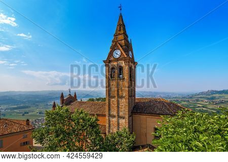 View from above on church's roof and old brick belfry with clock under blue sky in small town of Magliano Alfieri in Piedmont, Northern Italy.