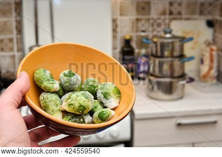 Frozen Brussels Sprouts In A Bowl On The Background Of The Kitchen. Hand Holding A Bowl Of Frozen Br