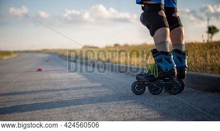 Roller skates. Inline skating on asphalt road in nature, Rollerblader and slalom cone