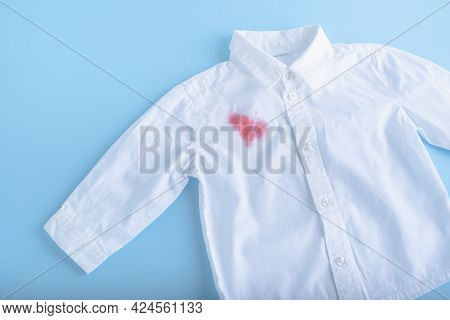 Juice Spilled On A White Shirt. Isolated On Blue Background