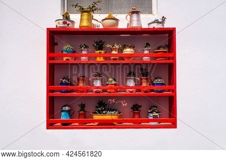 Wooden Red Shelf With Colorful Flowers, Plants And Pots On Exterior Whitewashed Wall Of A House In P