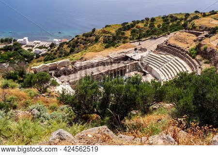 Ruins Of Ancient Theater Of Milos On A Green Hill With Mediterranean Sea In The Background Near Tryp
