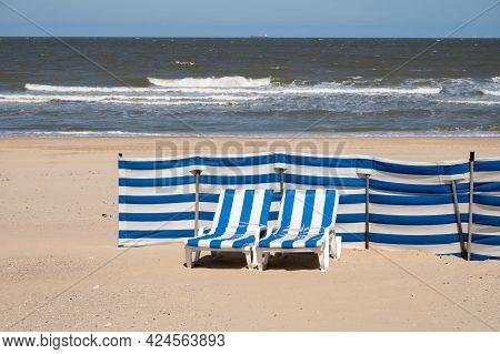 Blue-white Sun Beds On Yellow Sandy Beach In Small Belgian Town De Haan Or Le Coq Sur Mer, Luxury Va