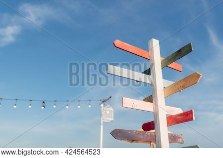 Guidepost With Bright Colored Arrows In The Sunlight With Blue Sky Background.