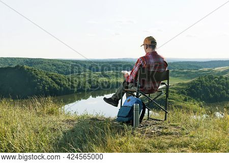 Man Hiker Solo On The Mountain  Reading Book. Caucasian Man Travel Relax In The Holiday.