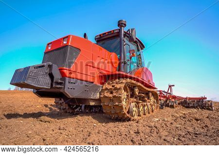 A Heavy Tracked Tractor Plows And Buries A Field In Early Spring Against The Blue Sky.