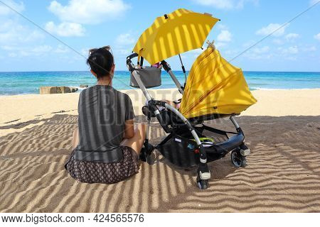 Young Brunette Mother With Yellow Baby Stroller (pram) And Umbrella Sitting On A Beach And Looking A