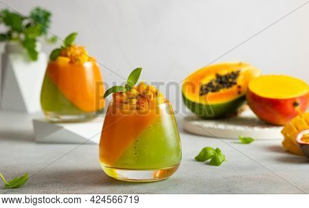 Summer dessert with exotic fruits. Mango, papaya, passion fruit and kiwi jelly dessert in glass.