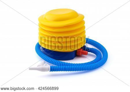 A Yellow And Blue Plastic Foot Pump With A Long Ruffled Hose And A White Nozzle Isolated On A Clean