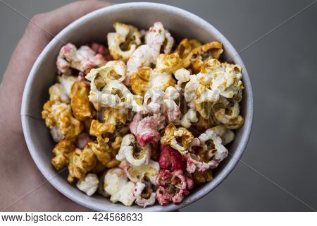 Popcorn Viewed From Above.  Eating Popcorn. Human Hand. Top View