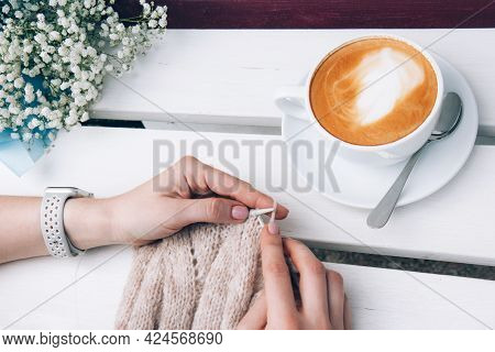 Female Hands With Knitting And White Cup Of Cappuccino With Latte Art. Knitting On Light Background.