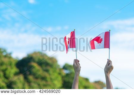 Hand Holding Canada Flag On Blue Sky Background. Canada Day  And Happy Celebration Concepts