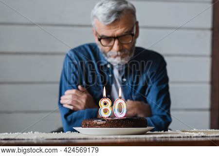 Birthday Cake With Burning Candles In Shape Of Eighty Numbers Near Senior Man On Blurred Background