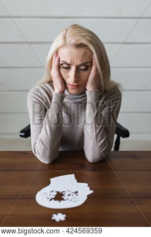 Upset Senior Woman With Alzheimer Looking At Puzzle On Blurred Foreground