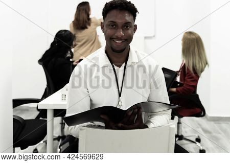 Confident Team Leader. African Young Man Holding Office Binder And Looking At Camera With Smile Whil